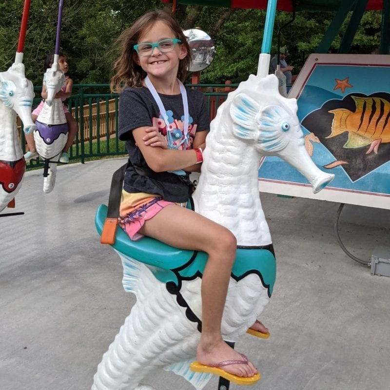 A young girl rides a seahorse on a carousel at Holiday World.